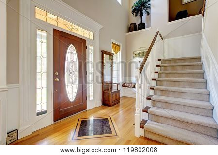 Nice Entryway To Home With Carpeted Staircase, And White Interior.