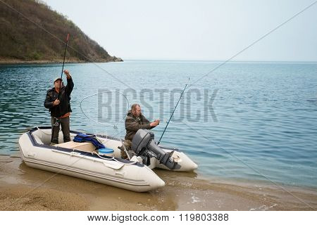 Fishermen on the sea in a boat fishing rods stacked. Coast Sea of Japan, Russia.