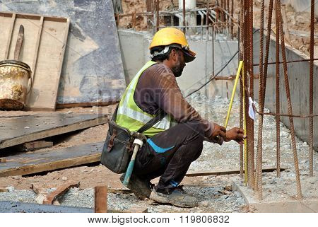 Construction workers fabricate steel reinforcement for concrete wall at the construction site