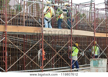 Construction workers fabricate steel reinforcement for concrete wall at the construction site.