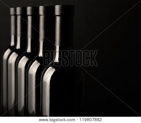 Different wine bottlenecks on dark background