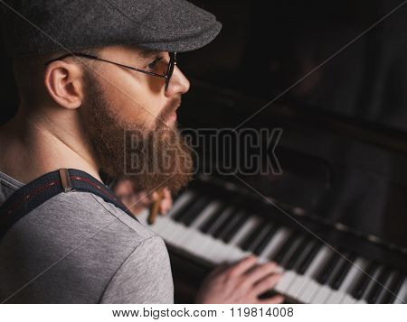 Talented bearded musician is playing the piano