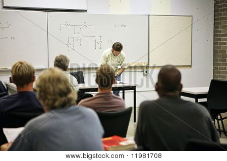 An adult education class in electricity.  Focus on the electrical circuit diagram on the board.