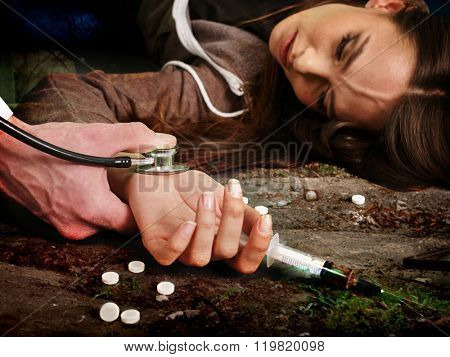 Unconscious woman addicted keeps syringe and lying on  dirty floor. Death from drugs concept.