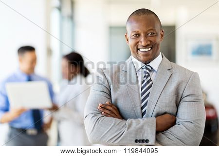 happy african salesman standing at car dealership with colleagues on background
