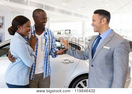 mid age car salesman handing over new car key to african couple in car showroom poster