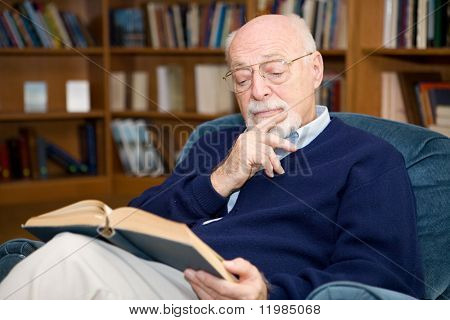 Closeup of senior man sitting in an easy chair and reading.