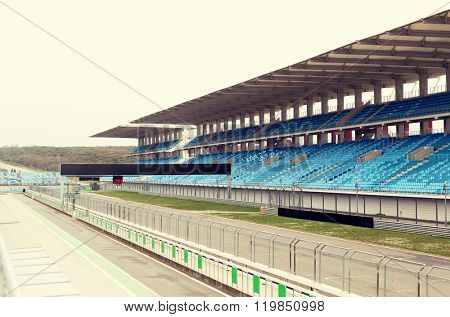 racing, motosports, extreme and motoring concept - empty speedway and bleachers on stadium