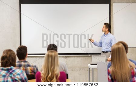 education, high school, technology and people concept - teacher standing with remote control, laptop computer in front of white board and students in classroom
