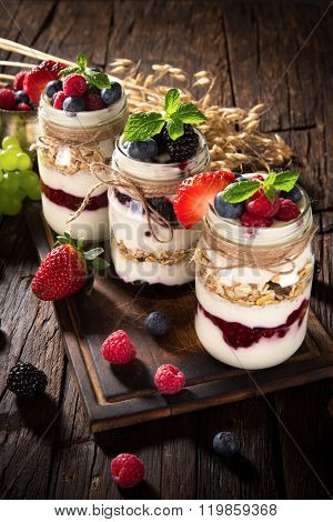 Tasty yoghurts with muesli, fresh berries and  jam on wooden table. Healthy breakfast.