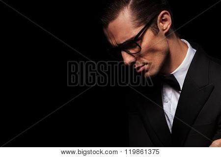 side portrait of classy elegant man in black suit posing in dark studio background looking down