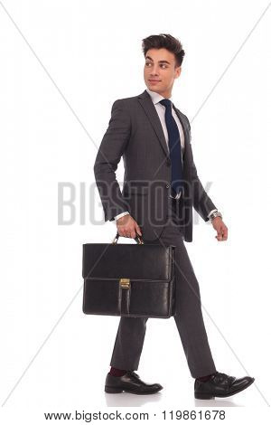 side view of a walking businessman looking back over his shoulder while holding a suitcase on white background