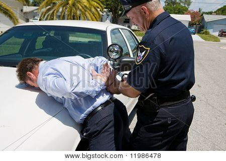 Police officer handcuffing and arresting a well dressed, white collar suspect.