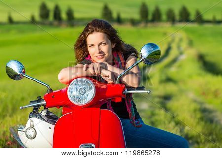 Portrait of toung beautiful woman with a scooter and tuscany landscape in background