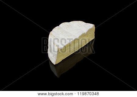 A Piece Of Camembert Cheese On Black Background