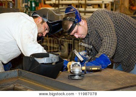 Due saldatori lavorano insieme su un progetto di difficile lavoro del metallo.  Autentico e preciso contenuto depi