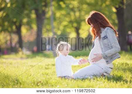 Pregnant woman and girl in the park