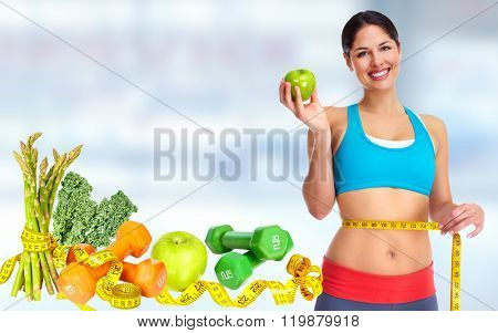 Woman measuring her waist size over blue background.