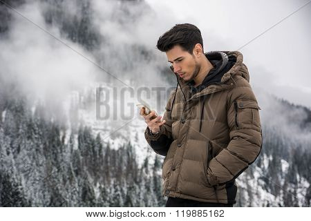 Young man in at mountain using cell phone