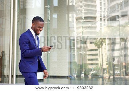 Happy Young Man Reading Text Message On His Mobile Phone