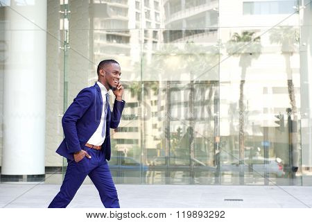 Happy Young Man Walking And Talking On Mobile Phone