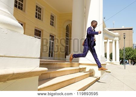 Young Businessman Running Out Of A Building