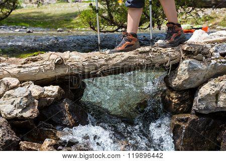 Feet of female hiker on bridge