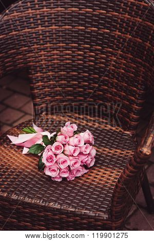 Pink roses bouquet on chair for date