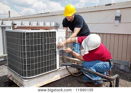 Dos trabajadores en la azotea de un edificio que trabaja en la unidad de aire acondicionado.