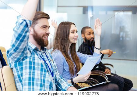 Cheerful young people sitting with raised hands and asking questions on business conference