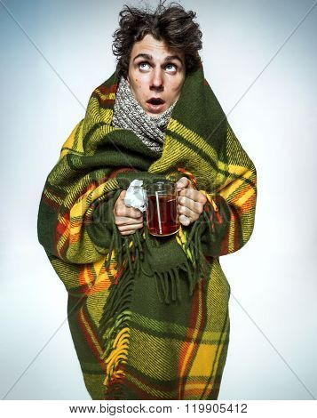 Ill Man Covered With Plaid Blanket With Hot Tea