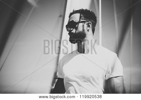 Portrait of young bearded man wearing sunglasses standing on the yacht in sunny day. Horizontal mock