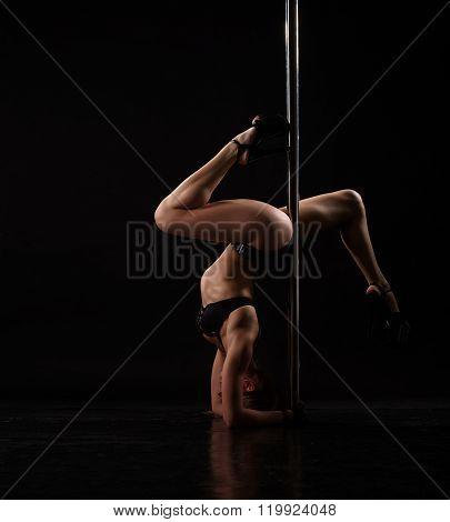 Seductive dancer doing handstand to pylon