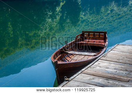 Wooden boat, sky and forest reflected in the mirror lake water