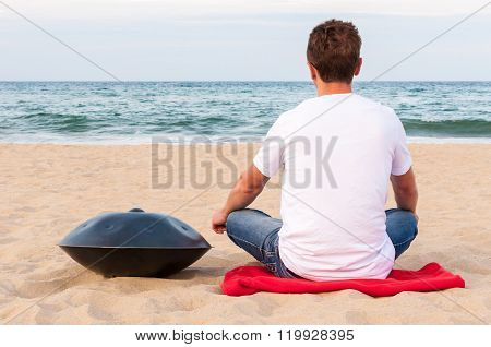 Young stylish guy sitting on the sand beach near handpan or hang with sea On Background. The Hang is