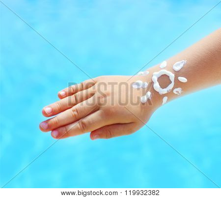 Little Hand Of The Baby With Suntan Lotion Near The Pool