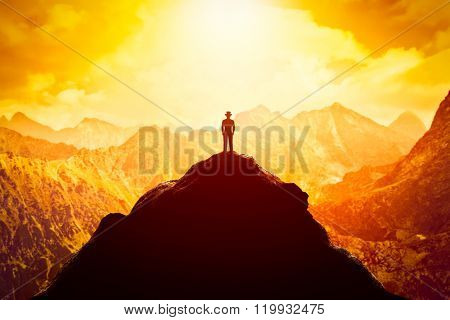 Businessman in hat on the peak of the mountain looking at sunset. Conceptual - business venture, future perspective, success, determination