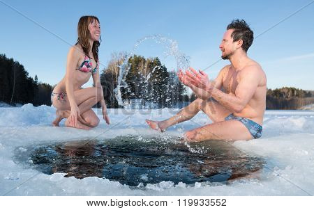 Young couple having fun near the ice hole on a winter frozen lake