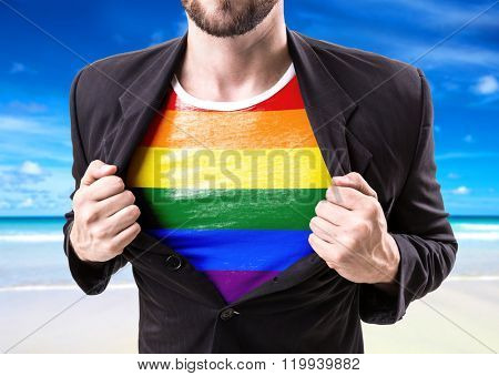 Businessman stretching suit with Rainbow Flag (LGBT Movement) with beach background