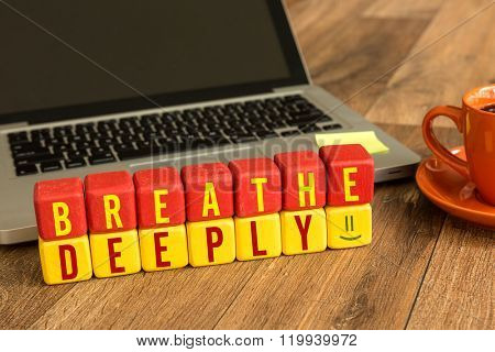 Breathe Deeply written on a wooden cube in a office desk