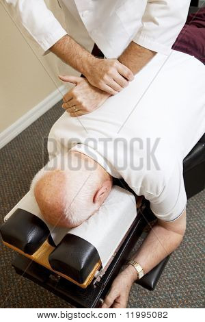 Closeup of chiropractors hands adjusting a senior man's spine.