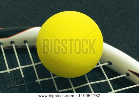 Racquetball On Racket Strings. Yellow Frontenis Ball Laying On Racket Strings.