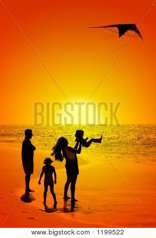 Familia y una cometa al atardecer