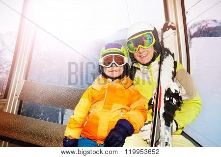 Mother and son in ski lift happy smile wear masks