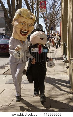 Asheville, North Carolina, USA - February 28, 2016: Humorous effigies of Hillary Clinton and Mr. Monopoly hold hands and carry money bags followed by marching Bernie Sanders supporters at a Bernie Sanders rally