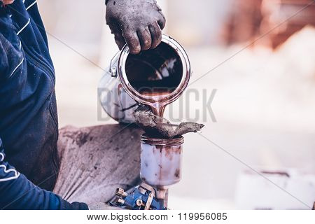 Industrial Worker Preparing Paint For Spraying With Spray Gun
