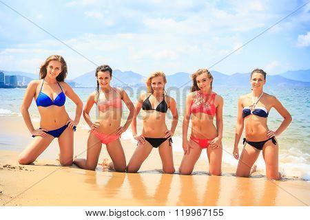 Cheerleaders In Bikinis Stand On Knees In Line On Wet Sand