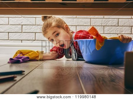 Charming little helper. Cute little child girl makes cleaning the house. Girl wipes the floor.