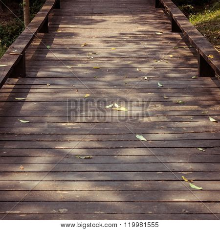 Old Wooden Walkway With Falling Leaves In The Morning Of Autumn Seasonal