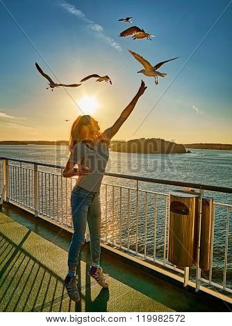 Young girl feeding seagulls in the flare of setting sun onboard a ferry